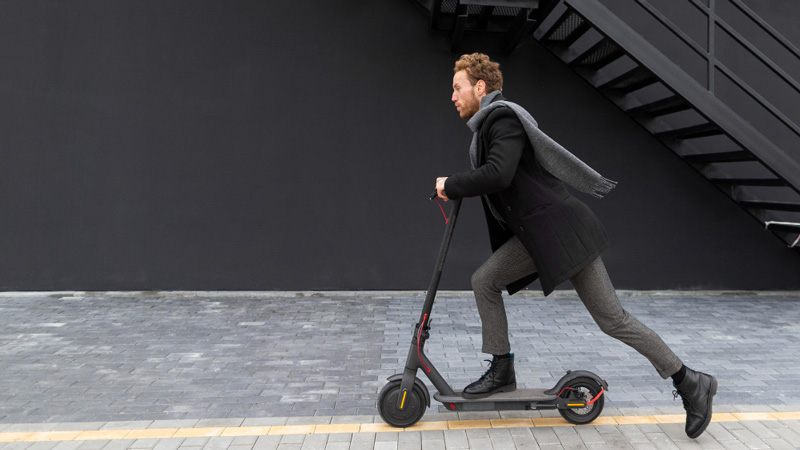 handsome male riding electric scooter