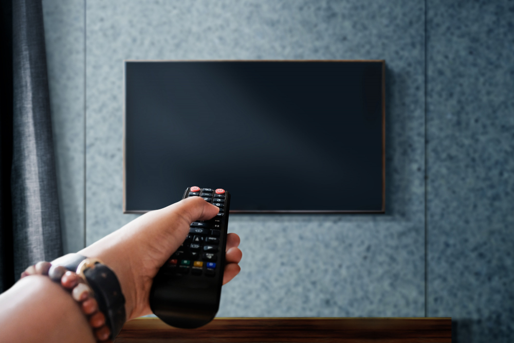 watching television concept hand holding tv s remote control changing channel